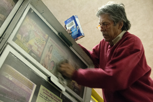 Eddie Munoz, owner of Strip Advertising, uses a lacquer thinner to clean news racks near Circus Circus Hotel in Las Vegas, Thursday, Oct. 24, 2013. An ordinance is being considered by Clark County ...