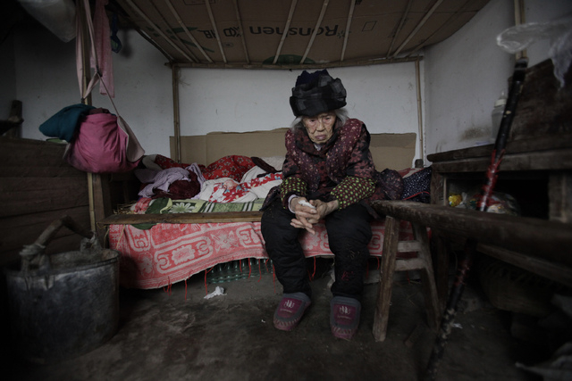 Zhang Zefang, a 94-year-old woman who sued her own children for not taking care of her, sits on her bed in her house in Fusheng Village, east of Chongqing City, China on March 19, 2013. Zhang is a ...
