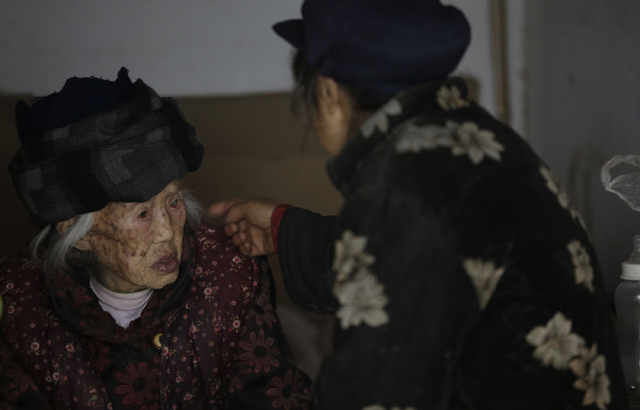 Zhang Zefang, a 94-year old woman who sued her own children for not taking care of her, left, and Kuang Shiying, Zhang's daughter-in-law, speak to each other at her house in Fusheng Village, east  ...