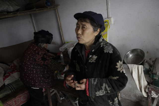 Zhang Zefang, a 94-year-old woman who sued her own children for not taking care of her, left, sits up from her bed, as her daughter-in law Kuang Shiying speaks at her house in Fusheng Village, eas ...