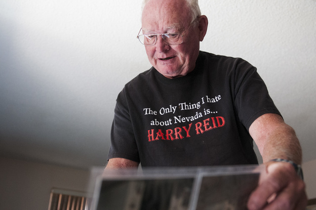 Bob Hitchcock, is seen looking through a photo album with photos of his home at Stewart's Point in Lake Mead National Recreation Area, Saturday, Oct. 5, 2013, in Las Vegas, Nev. Hitchcock was orde ...