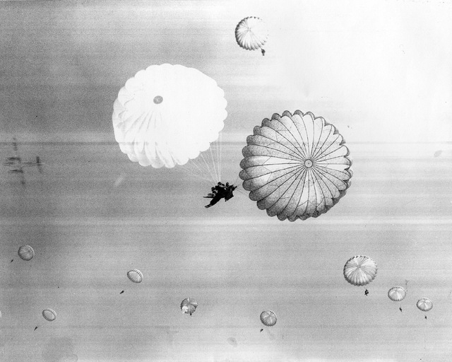This archive photo shows Army paratrooper Al Tseu, center, and others jumping into the aftermath of an atomic blast. The former 82nd Airborne Division soldier is one of the featured speakers at th ...