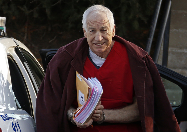 Former Penn State assistant football coach Jerry Sandusky is shown Jan. 10 at the Centre County Courthouse in Bellefonte, Pa. Penn State officials said Monday that it is paying $59.7 million to 26 ...