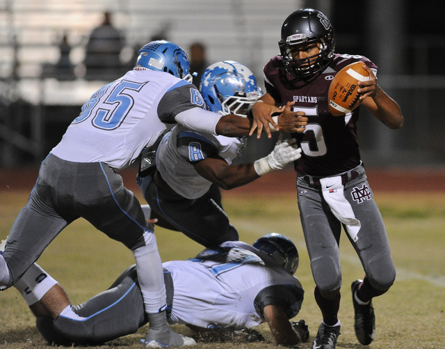 Cimarron's Derek Morefield (5) is surrounded by a host of Centennial defenders including Andre Diller (85) and Haikeem Arnold (8) during a football game at Cimarron-Memorial High School in Las Veg ...