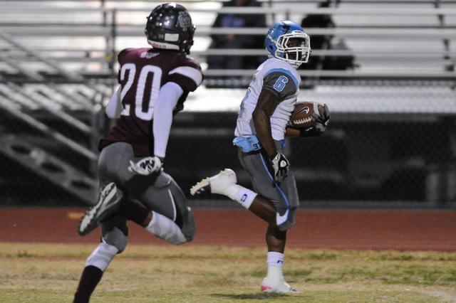 Centennial's Lantz Worthington (6) races past Cimarron defender Savigon McIver (20) for a touchdown run during a football game at Cimarron-Memorial High School in Las Vegas Thursday, Oct. 24, 2013 ...