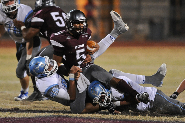Cimarron's Derek Morefield (5) is brought down by Centennial defender Andre Diller (85) during a football game at Cimarron-Memorial High School in Las Vegas Thursday, Oct. 24, 2013. (David Clevela ...