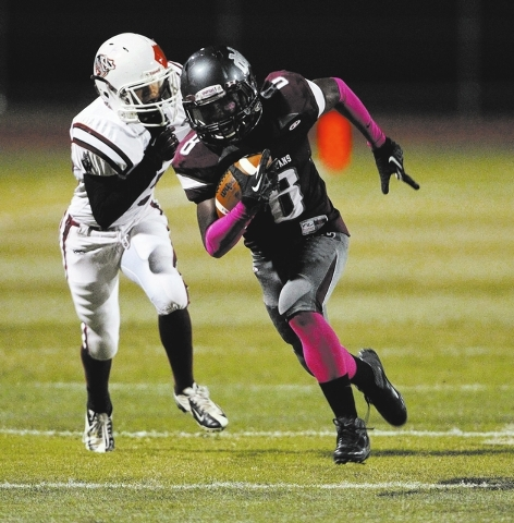Cimarron-Memorial wide receiver Maurice Bennett runs ahead of Desert Oasis defensive back Hunter Amos for a 48-yard touchdown in the first quarter of their football game at Cimarron-Memorial High  ...
