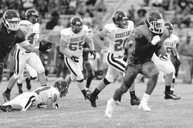 Legacy running back Casey Hughes (24) breaks free from Hurricane defensive back Jay Williams (21) and runs for a second quarter touchdown during a football game at Legacy High School, North Las Ve ...