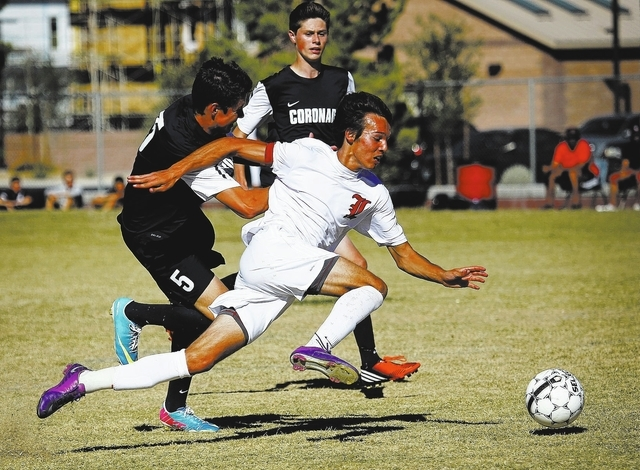 Liberty forward Danny Musovski battles past a pair of Coronado defenders to score a goal during their soccer game in Henderson on Oct. 2, 2013. (Jason Bean/Las Vegas Review-Journal)