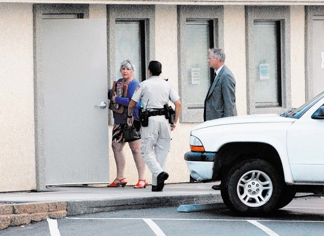 Shirley Matson with NCSO deputy and FBI agent entering the Assor's office (Horace Langford Jr. / Pahrump Valley Times)