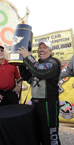 "John Force hoists the trophy after clinching the NHRA Funny Car season championship Sunday. Force has 2,581 points with one race remaining. ""I wanted to prove I can still race and I can still wi ..."