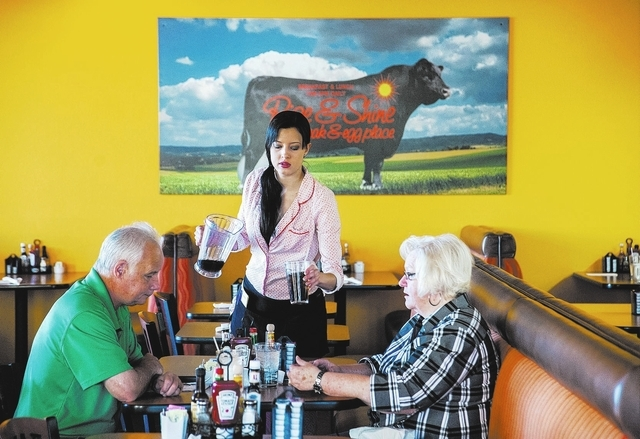 Shannon Miller, server, from Rise & Shine, a Steak and Egg Place, center, refills a customers beverage, at their restaurant located at 10690 Southern Highlands Parkway 89141, in Las Vegas, Friday, ...
