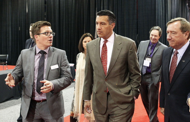 Nevada Gov. Brian Sandoval, center, talks with Nigel Mayes, vice president of UBM Aviation Routes, Ltd, left, and Rossi Ralenkotter, president and ceo of the Las Vegas Convention and Visitors Auth ...