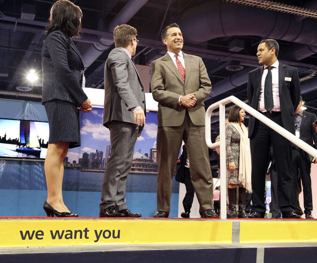 Nevada Gov. Brian Sandoval, center, looks out over the array of booths at the World Routes Conference at the Las Vegas Convention Center, Monday, Oct. 7, 2013. Standing with the governor are: left ...
