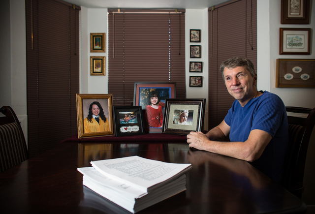 Former State Sen. Bob Ryan poses at his Las Vegas home alongside photos of his granddaughter and a stack of paperwork Friday, Sept. 20, 2013. Ryan is upset with the Nevada Division of Insurance an ...