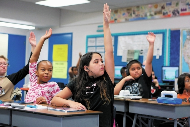 Aidan Patterson, center, pauses from working on an iPad to raise her hand with other students in Steve Armitage's 5th grade class at Hancock Elementary School Friday, Oct. 18, 2013, in Las Vegas ...