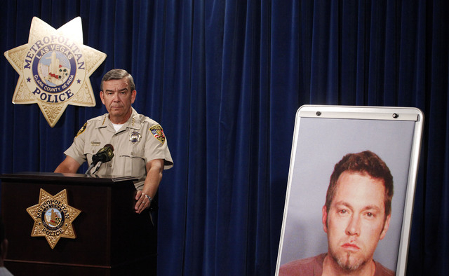 Clark County Sheriff Doug Gillespie addresses the media at Las Vegas Pol;ice headquarters about the shooting that occurred inside Bally's on Monday, Oct. 21, 2013. Next to Gillespie is a picture o ...