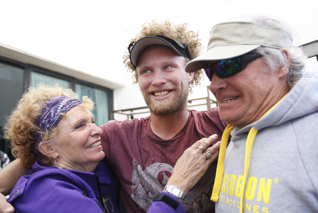 Daredevil slackline athlete Andy Lewis, middle, reunites with his parents Lynn and Roger Lewis after setting the world record for the longest urban highline walk outside the 63rd floor of the Mand ...
