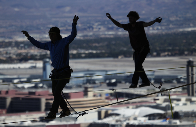 With McCarran Airport in the background, daredevil slackline athletes Mickey Wilson, left, and Andy Lewis participate in a urban highline walk outside the 63rd floor of the Mandalay Bay in Las Veg ...