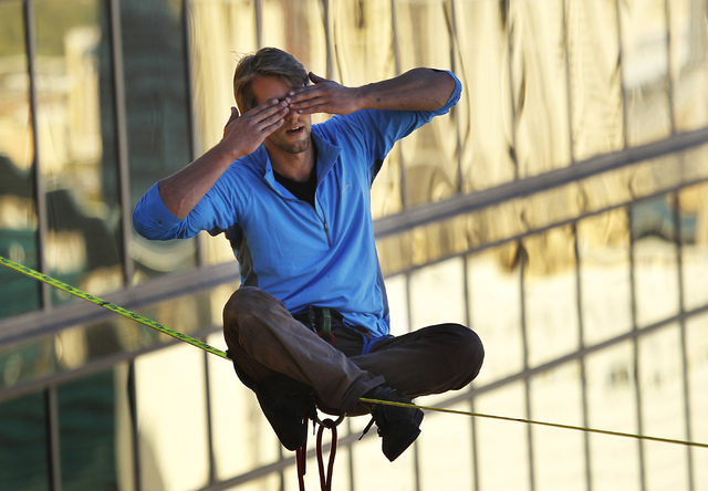 Daredevil slackline athlete Hayden Nickell closes his eyes while sitting down for a break during an urban highline walk outside the 63rd floor of the Mandalay Bay in Las Vegas on Oct. 16 , 2013. ( ...