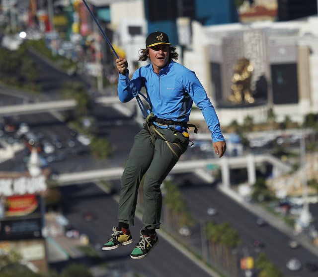 With the Strip in the background, daredevil slackline athlete Mickey Wilson swings from his safety line while taking a brake from an urban highline walk outside the 63rd floor of the Mandalay Bay  ...