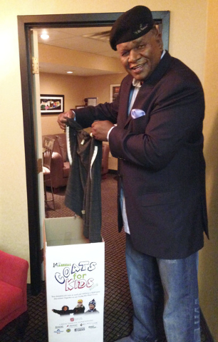 Comedian George Wallace takes a moment to add a jacket to the Coats for Kids collection box Sept. 20. Residents will find Coats for Kids boxes at Albertsons stores and are asked to donate children ...