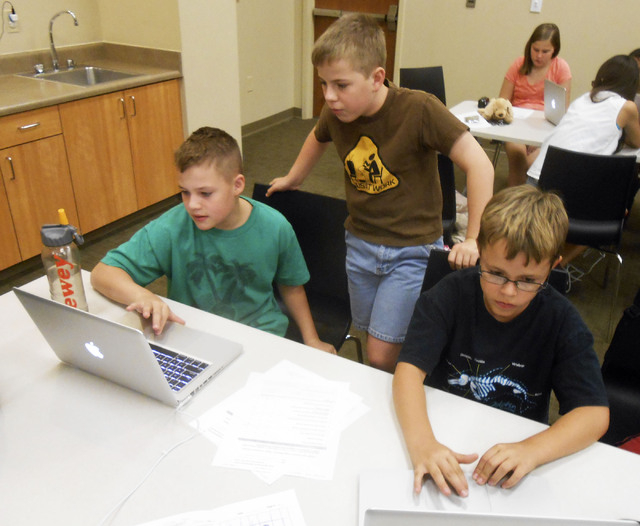 From left, Dewey, 11; Andy, 12; and Reno, 10, work on their TechArt Studio project at the Centennial Hills Library, Sept. 29. The two-day program teaches kids the elements of movie making, and par ...