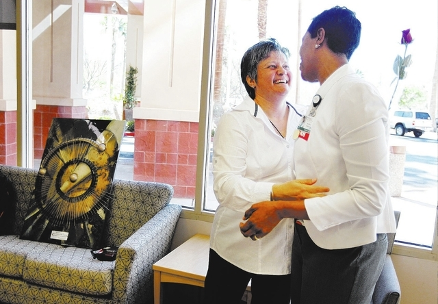 Artist Violeta Veltcheva, left, donates an original piece of work, seen on the couch behind her, to Southern Hills Hospital's Chief Nursing Officer Maura Wright, right, in Las Vegas on Oct. 17, 20 ...