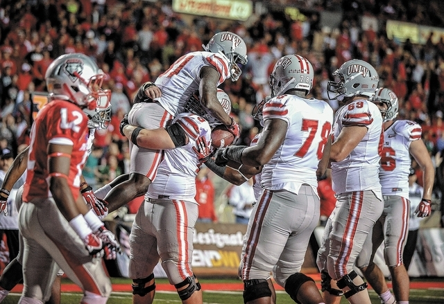 UNLV'S Devante Davis,middle, is hugged by teammates after scoring another touchdown against New Mexico Saturday evening at University stadium. (Albuquerque Journal/Roberto E. Rosales)