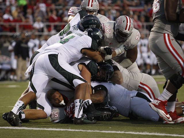 UNLV running back Tim Cornett lies at the bottom of a pile without his helmet after he was tackled by Hawaii at Sam Boyd Stadium in Las Vegas Saturday, Oct. 12, 2013. (John Locher/Las Vegas Review ...