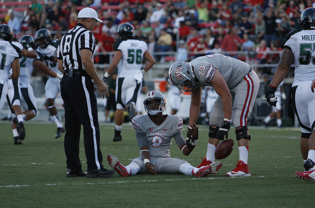 UNLV quarterback sits on the ground after he was sacked during a game against Hawaii at Sam Boyd Stadium in Las Vegas Saturday, Oct. 12, 2013. (John Locher/Las Vegas Review-Journal)