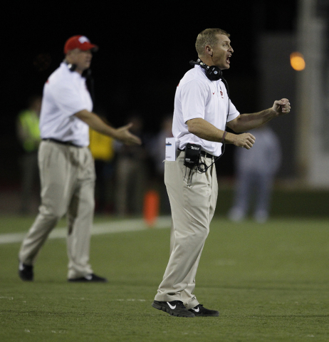 UNLV head coach Bobby Hauck, right, yells at his players during their game against Hawaii at Sam Boyd Stadium in Las Vegas Saturday, Oct. 12, 2013. (AP Photo/Las Vegas Review-Journal, John Locher)