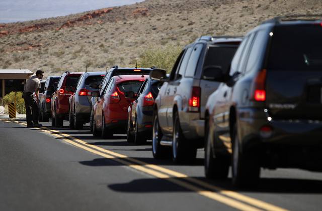 """Park Ranger Chris Johnson speaks to visitors lined up at the entrance of Valley of Fire State Park about 50 miles northeast of Las Vegas Friday, Oct. 11, 2013. """"We've just been flooded with v ..."""