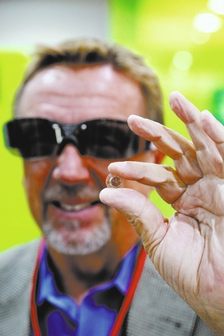 Dr. Jerry Legerton shows the special contact lens which is integral to his iOPTIK technology at the Vision Expo West, in the Sands Expo Center of Las Vegas, Nev. on Oct. 4, 2013. The International ...