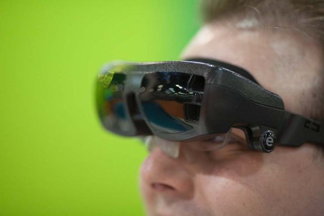 eSight rep Tyler Moore models his eSight vision system which helps him see despite being legally blind at the Vision Expo West, in the Sands Expo Center of Las Vegas, Nev. on Oct. 4, 2013. The Int ...