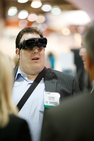 Legally blind eSight rep Tyler Moore discusses his eSight vision system, which allows him to see, with show attendees at the Vision Expo West, in the Sands Expo Center of Las Vegas, Nev. on Oct. 4 ...