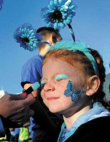"Makenzie Garner, 5, gets a little made up before beginning One Drop's second annual ""Walk for Water"" along South Las Vegas Blvd. on Saturday, Oct. 5, 2013.  One Drop, established by Cirq ..."