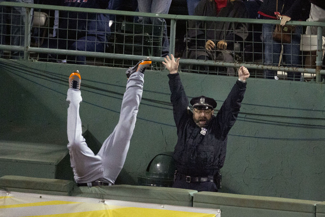 In this Oct. 13, 2013 photo, fans and Boston Police officer Steve Horgan celebrate as Detroit Tigers' Torii Hunter falls over the right field fence into the bullpen trying to catch a grand slam hi ...