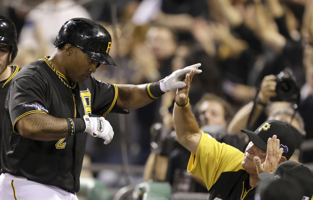 Pittsburgh Pirates' Marlon Byrd, left is greeted by manager Clint Hurdle after hitting a home run against the Cincinnati Reds in the second inning of the NL wild-card playoff baseball game Tuesday ...