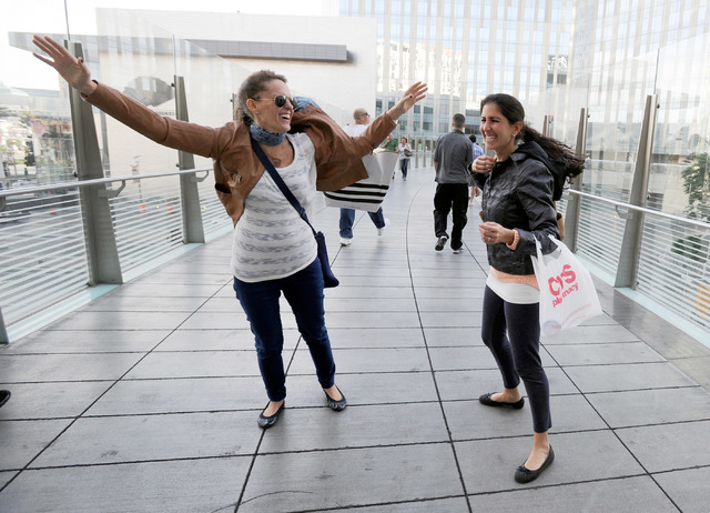 Sisters Sally, left, and Judith Amkie of Mexico battle the gusty winds along a bridge at CityCenter on Monday. (David Becker/Las Vegas Review-Journal)