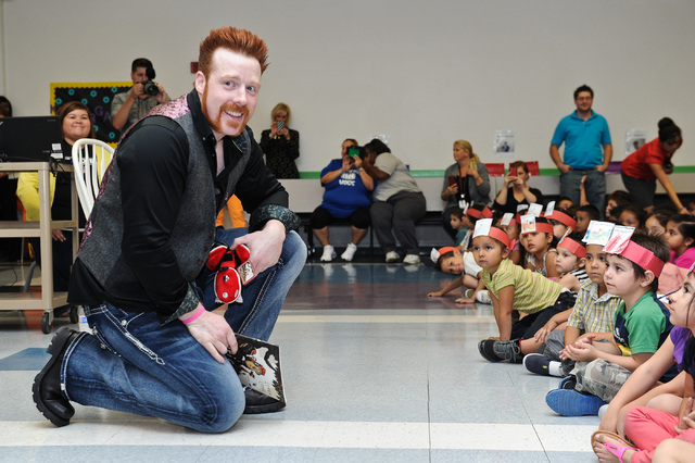 "WWE Superstar Sheamus, left, reads the book ""Otis"" to children at Gragson Elementary School in Las Vegas Thursday, Oct. 3, 2013.  Jumpstart's Read for the Record is a world-record-breaki ..."
