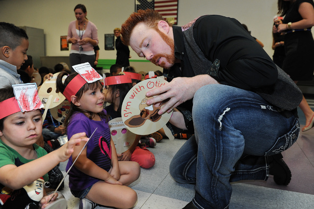 Four-year old Emily Damian, left, interacts with WWE Superstar Sheamus after a book reading at Gragson Elementary School in Las Vegas Thursday, Oct. 3, 2013.  Jumpstart's Read for the Record is a  ...