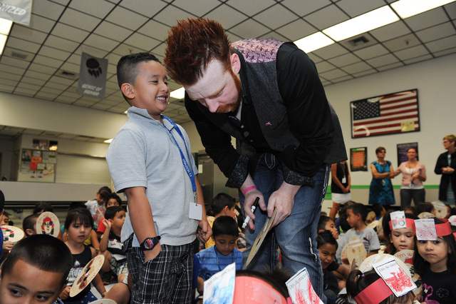 Five-year old Julius Flores, left, whispers to WWE Superstar Sheamus after a book reading at Gragson Elementary School in Las Vegas Thursday, Oct. 3, 2013.  Jumpstart's Read for the Record is a wo ...