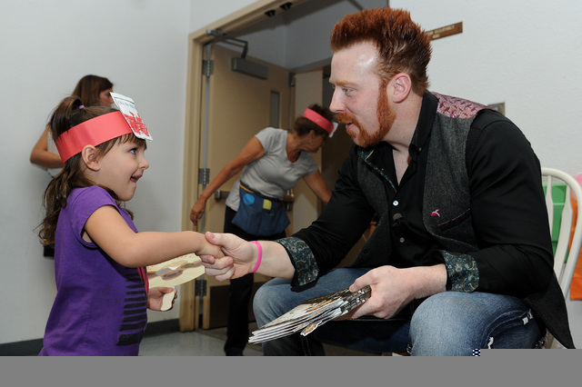 Four-year old Emily Damian, left, shakes hands with WWE Superstar Sheamus after a book reading at Gragson Elementary School in Las Vegas Thursday, Oct. 3, 2013.  Jumpstart's Read for the Record is ...