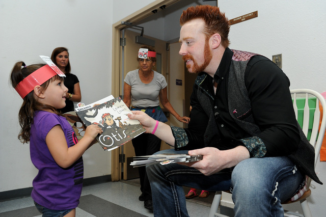 "Four-year old Emily Damian, left, receives a copy of ""Otis"" from WWE Superstar Sheamus after a book reading at Gragson Elementary School in Las Vegas Thursday, Oct. 3, 2013.  Jumpstart's ..."