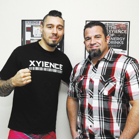 MMA boxer Dan Hardy, left, and John Villari, creative director for Xyience, pose next to two Xyience posters at Forte Creative Media P.R. in Las Vegas, Wednesday, Oct. 2, 2013. (Jerry Henkel/Las V ...