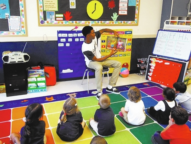 Justin Burks of the Arbor View High School basketball team reads to 4- and 5-year-olds Sept. 18, 2013, when the team visited Merryhill School, 7605 Grand Teton Drive. SPECIAL TO VIEW
