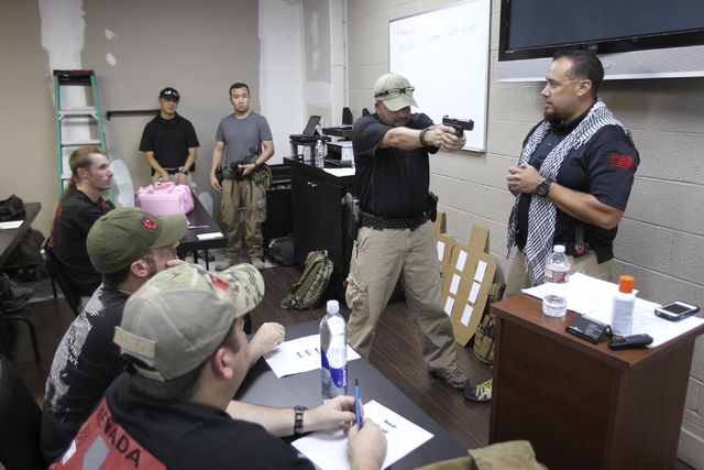 Zombie Eradication Response Team Chief Executive Officer Aaron Mauldin, right, and Assistant Instructor Chad Timney teach a pistol class at American Shooters at 3440 Arville St. in Las Vegas Frida ...