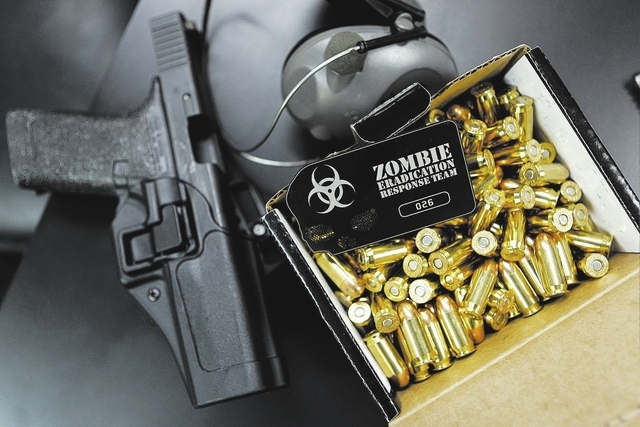 A Zombie Eradication Response Team member shows his card, weapon and ammunition during a pistol class at American Shooters at 3440 Arville St. in Las Vegas Friday, Aug. 20, 2013. Z.E.R.T. is a wor ...