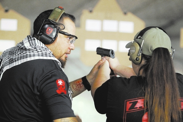 Zombie Eradication Response Team Chief Executive Officer Aaron Mauldin, left, teaches Z.E.R.T. member Shannon Sensi during a pistol class at American Shooters at 3440 Arville St. in Las Vegas Frid ...